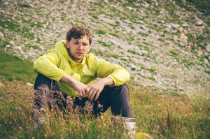 Man relaxing in mountains sitting on grass valley Traveling hiking summer recreation