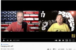 Jim Watkins til høyre og en annen tilhenger av Q, snakker om kirken og USA. Legg merke til reklamene bak JW. Q, 17 fordi Q er den 17nde bokatsvan i alfabetet. 8 fordi det er konspirasjonskanalen der det ikke er sensur som han er leder for. Er han også Q selv?